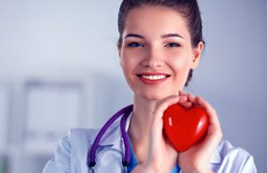 A nurse holding a heart shaped object to depict chronic care management