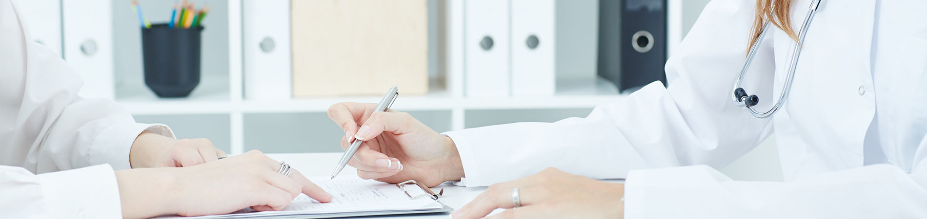 A doctor signing something at a medical practice