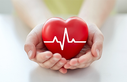 A hand holding a heart to represent a physician's promise with the million hearts initiative