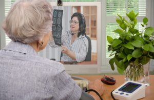 An older patient uses telehealth solutions to communicate with her doctor from the comfort of her home.