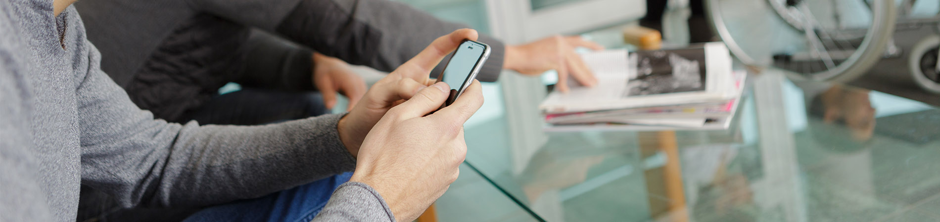 A young male patient utilizing digital check-ins at an appointment on his cellular device.