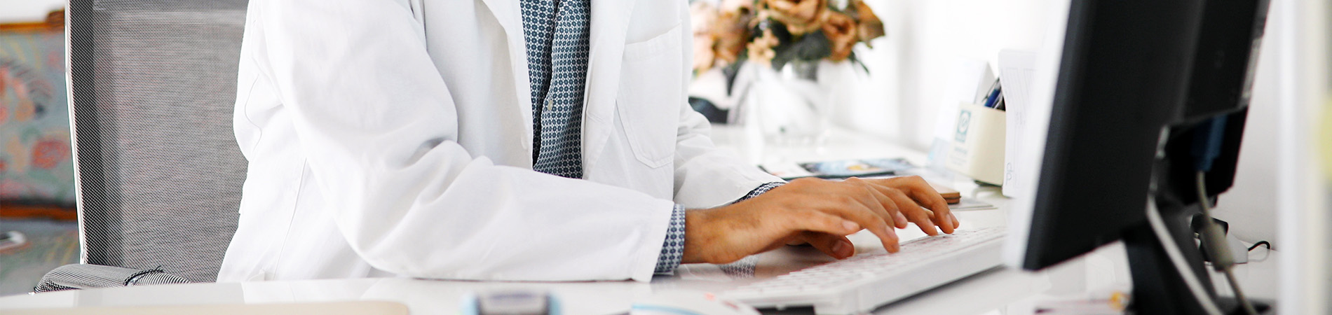 Happy male doctor staring at a computer screen avoiding HIPAA violations