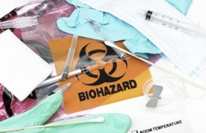 medical waste disposal represented with a pile of medical waste and the biohazard symbol