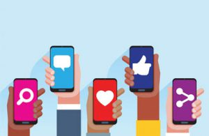 Social media icons on five different phones held in hands