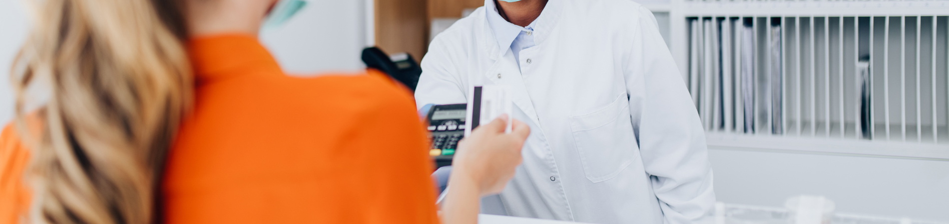 a woman using a payment processor to make a payment at a medical practice with a female practitioner
